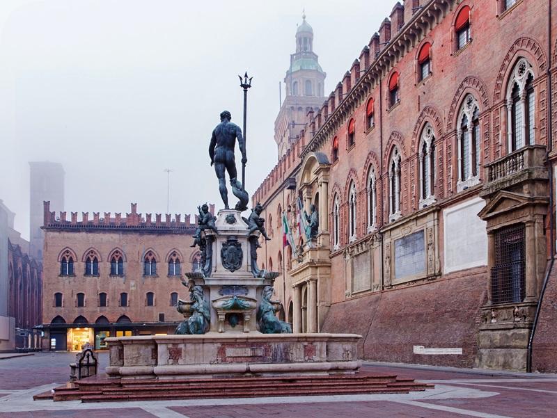 Bologna - Fontana di Nettuno or Neptune fountain on Piazza Maggiore square and Palazzo Comunale in fogy morning
